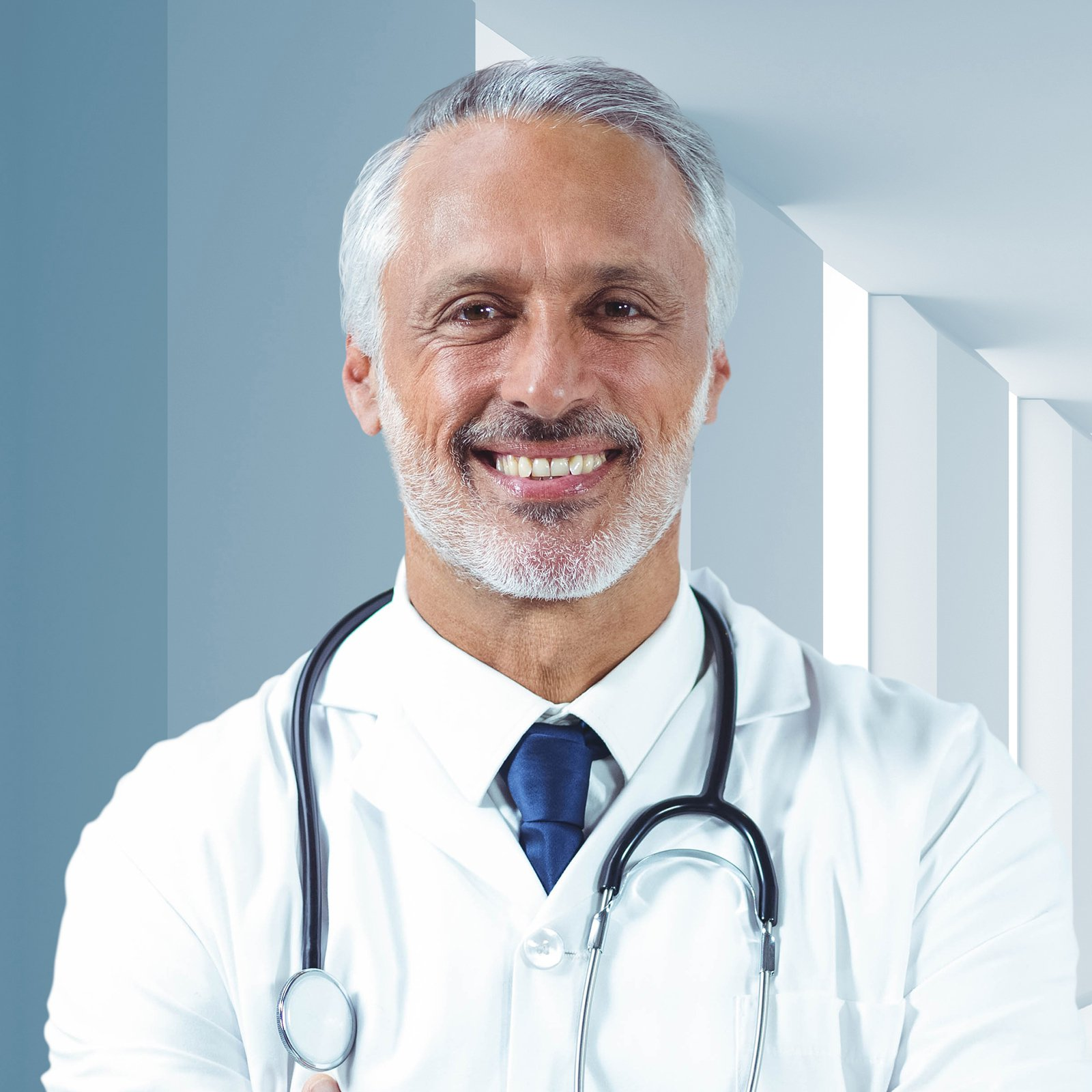 Male doctor standing with arms crossed in corrirdor